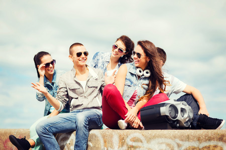 boom box: summer holidays and teenage concept - group of teenagers hanging out