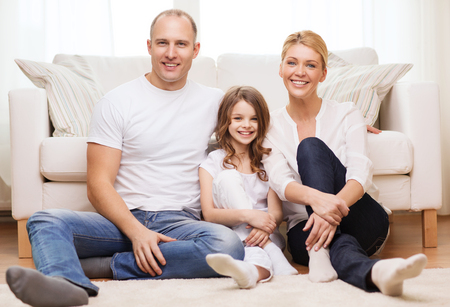 family, child and home concept - smiling parents and little girl sitting on floor at home photo
