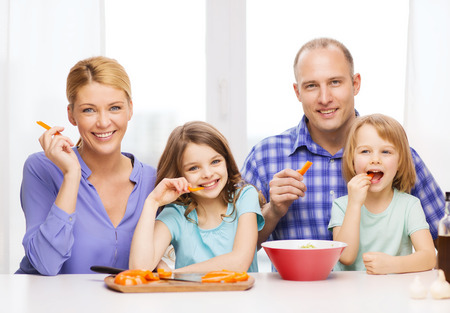 food, family, children, hapiness and people concept - happy family with two kids eating at home photo