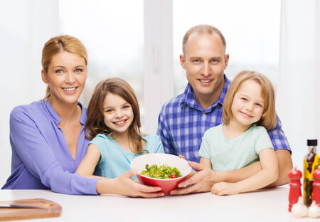 food, family, children, hapiness and people concept - happy family with two kids with salad at home photo