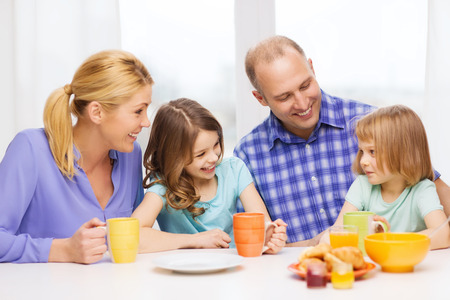 food, family, children, hapiness and people concept - happy family with two kids having breakfast at home photo