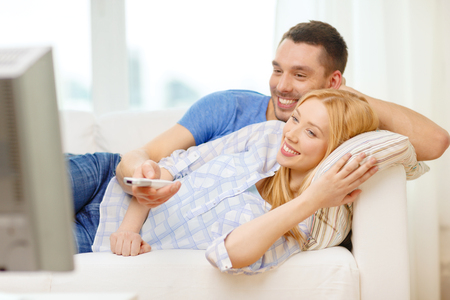 living room boy: love, family and happiness concept - smiling couple watching movie at home