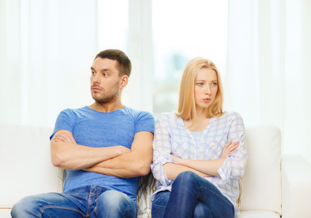 emotional couple: love, family and happiness concept - unhappy couple not speaking after having argument at home