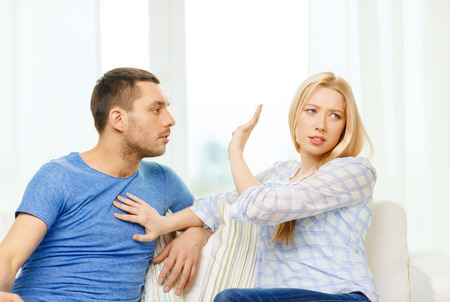 love, family and happiness concept - unhappy couple having argument at home photo
