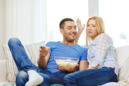 food, love, family and happiness concept - smiling couple with popcorn choosing what to watch at home photo