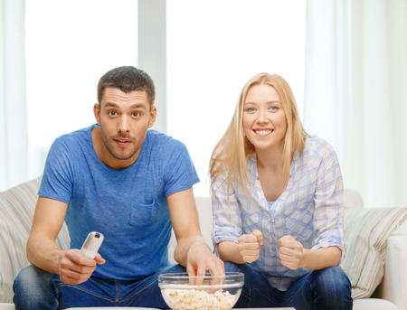 watching football: food, love, family, sports, entretainment and happiness concept - smiling couple with popcorn cheering sports team at home