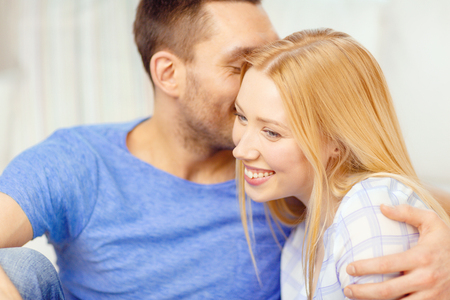 telling: love, family and happiness concept - man kissing young woman at home