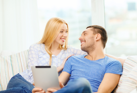 love, family, technology, internet and happiness concept - smiling happy couple witl tablet pc computer at home photo