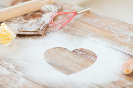 cooking and love concept - close up of heart of flour on wooden table at home photo