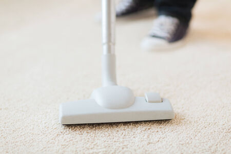 cleaning and home concept - close up of male hoovering carpet Stock Photo