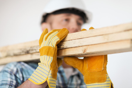 working gloves: repair, building and home concept - close up of male in gloves and helmet carrying wooden boards on shoulder Stock Photo