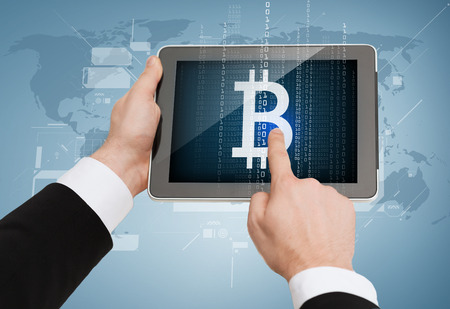 business, internet and technology concept - close up of man hands touching tablet pc with bitcoin symbol Stock Photo