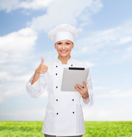 cooking, technology and food concept - smiling female chef, cook or baker with tablet pc computer showing thumbs up photo
