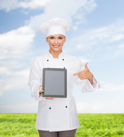 cooking, technology and food concept - smiling female chef, cook or baker with tablet pc computer blank screen photo