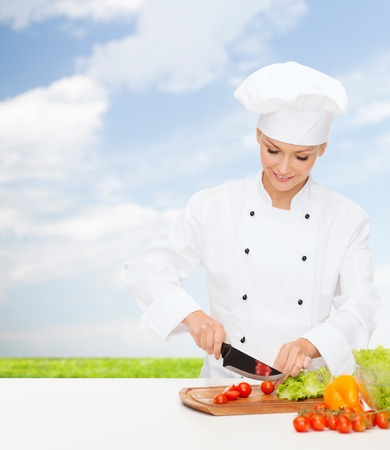 cooking and food concept - smiling female chef, cook or baker chopping vegetables photo