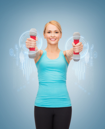 sport, excercising and healthcare concept - young sporty woman with light dumbbells photo