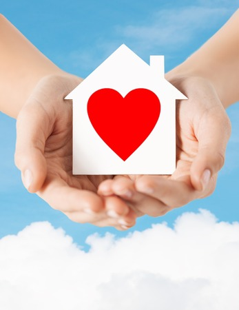 charity, real estate and family home concept - closeup picture of female hands holding white paper house with red heart photo