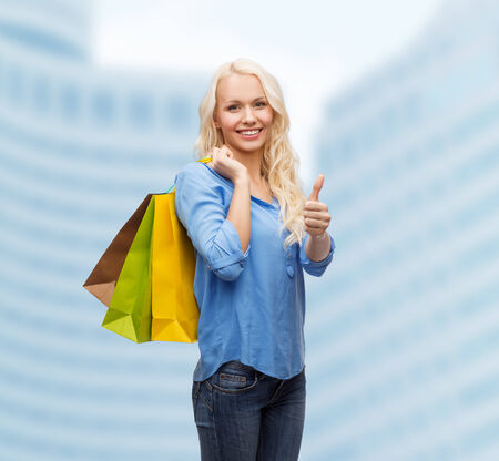 retail, gesture and sale concept - smiling woman with many shopping bags showing thumbs up photo