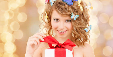health, holidays and beauty concept - happy teenage girl with butterflies in hair opening gift box photo