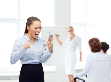 business, technology and education concept - screaming businesswoman with smartphone in office photo
