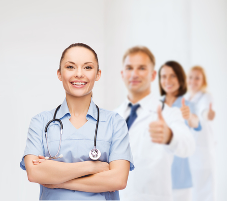 healthcare and medicine concept - smiling female doctor or nurse with stethoscope and team on the back showing thumbs up photo