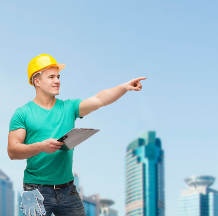repair, construction and maintenance concept - smiling man in helmet with clipboard pointing finger photo