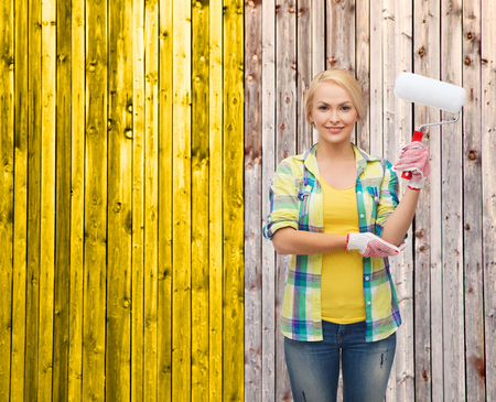 repair, construction and maintenance concept - smiling woman in gloves with paint roller photo