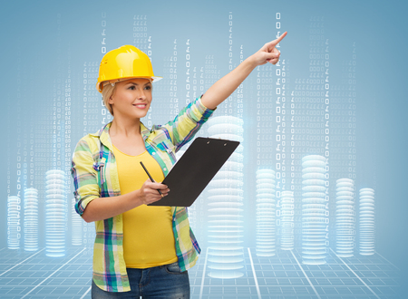 making notes: repair, construction and maintenance concept - smiling woman in helmet with clipboard pointing finger Stock Photo