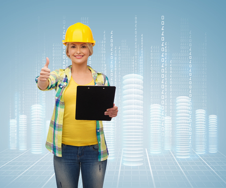 repair, construction and maintenance concept - smiling woman in helmet with clipboard showing thumbs up photo