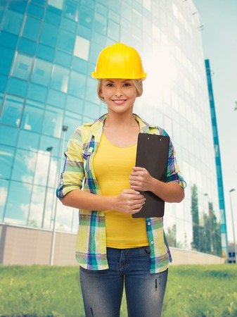 safety gear: repair, construction and maintenance concept - smiling woman in helmet with clipboard