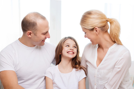 family, child and home concept - smiling parents and little girl at home photo