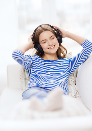 technology, music and happiness concept - smiling young girl in headphones at home photo
