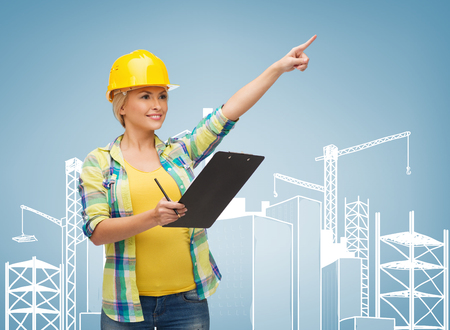 repair, construction and maintenance concept - smiling woman in helmet with clipboard pointing finger photo