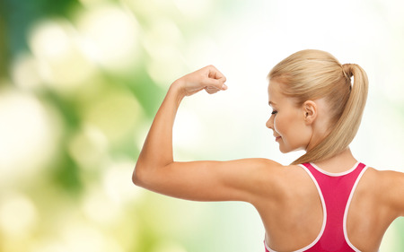 bicep: fitness and healtcare concept - young sporty woman showing her biceps Stock Photo