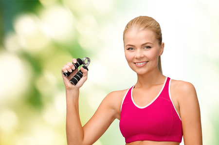 hand grip: fitness, healthcare and dieting concept - beautiful sporty woman with hand expander