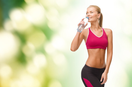 people drinking water: fitness, healthcare and dieting concept - smiling sporty woman with bottle of water Stock Photo