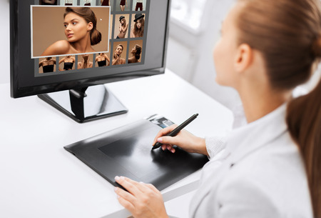 retouch: photography, office and magazine concept - female retoucher with drawing tablet and computer working at home or office