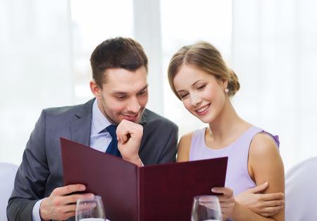 restaurant, echtpaar en vakantie concept - lachende echtpaar met menu in het restaurant
