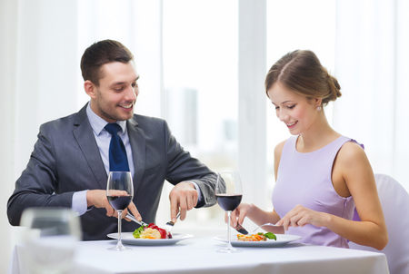 restaurant, couple and holiday concept - smiling couple eating main course with red wine at restaurant photo