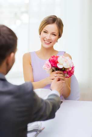 recieving: restaurant, couple and holiday concept - smiling woman recieving bouquet of flowers from husband or boyfriend at restaurant