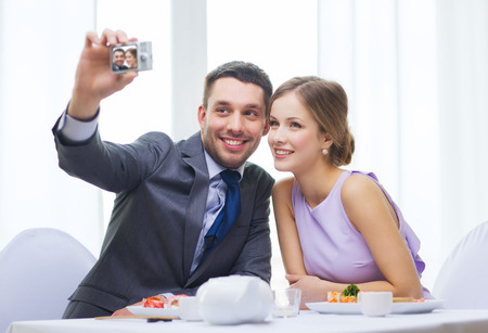 restaurant, couple, technology and holiday concept - smiling couple taking self portrait picture with digital camera at resaturant photo