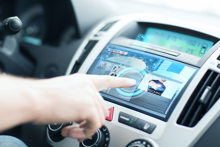 electrical system: transportation and vehicle concept - man using car control panel to read news Stock Photo