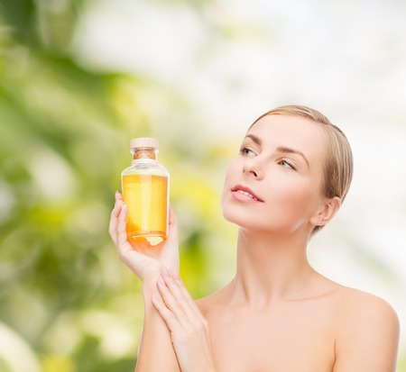 bath essence: health, spa and beauty concept - lovely woman with oil bottle