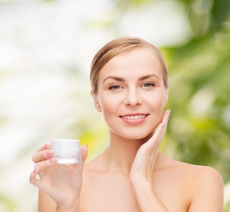 mujer maquillandose: cosméticos, salud y el concepto de belleza - mujer hermosa que aplica la crema en su piel