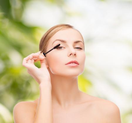 化粧品、健康と美容のコンセプト - マスカラーと美しい女性