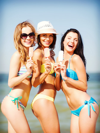 summer holidays and vacation - girls in bikini with ice cream on the beach photo