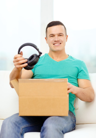 recieve: post, home, technology and lifestyle concept - smiling man opening cardboard box with headphones in it