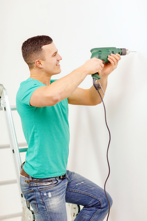 making hole: repair, building and home concept - smiling man with electric drill making hole in wall Stock Photo