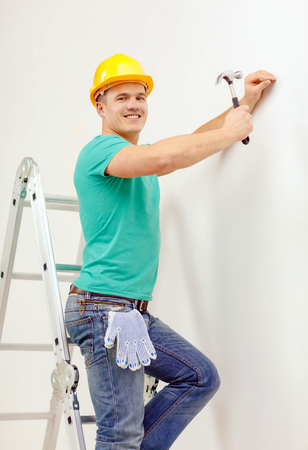 reapir, building and home renovation concept - smiling man in yellow protective helmet hammering nail in wall photo