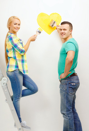 renovating: repair, building and home concept - smiling couple painting small heart on wall at home Stock Photo
